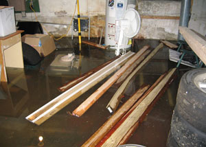 A severely flooding basement in Winter Park, with lumber and personal items floating in a foot of water